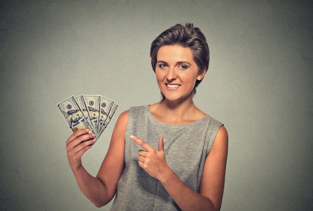financial reward: Closeup portrait super happy excited successful young woman holding money dollar bills in hand isolated on gray wall background. Positive human emotion facial expression feeling. Financial reward Stock Photo