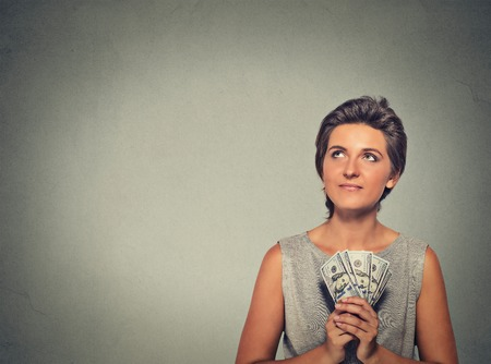 woman holding money: Closeup portrait happy excited successful young woman holding money dollar bills in hand looking up isolated on gray wall background. Positive emotion facial expression feeling. Financial reward Stock Photo