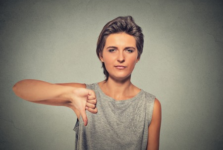 dislike: Closeup portrait of unhappy, angry, mad, pissed off woman, annoyed giving thumbs down gesture looking with negative facial expression, disapproval, isolated on gray background. Human emotions attitude Stock Photo