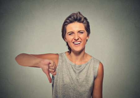 attitude girls: Closeup portrait sarcastic young woman showing thumbs down sign hand gesture, happy someone made mistake, lost, failed isolated on gray background. Human emotion, facial expression, feelings attitude