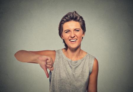 pobre: Retrato del primer sarcásticos joven mujer que muestra los pulgares abajo firma gesto de la mano, feliz alguien hizo error, perdido, no aislado en fondo gris. La emoción humana, la expresión facial, la actitud de los sentimientos