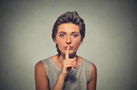 shush: Closeup portrait of secret woman. Young female showing hand silence sign, asking someone to keep it quiet, isolated on gray background. Human communication, facial expressions signs Stock Photo