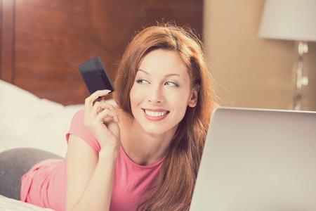 tarjeta de credito: Mujer con el ordenador portátil compras en línea de la celebración que muestra la tarjeta de crédito