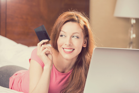 rewards: woman with laptop shopping on line holding showing credit card