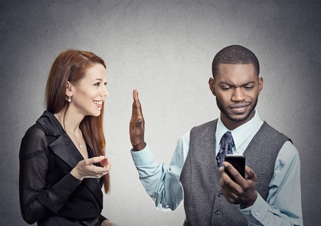 negociacion: Siendo atractiva mujer ignoró detenido por hombre hermoso joven que mira smartphone internet navegación lectura aislada en el fondo gris de la pared. Concepto de adicción de teléfono. Cara humana emociones de la expresión Foto de archivo