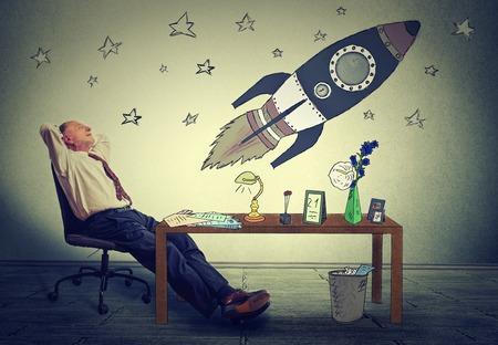 成熟したビジネスの男が彼のオフィスの机でリラックス。幸せな上級ビジネスマンが会社繁栄のアームチェア空想の上に座って。将来の宇宙観光の