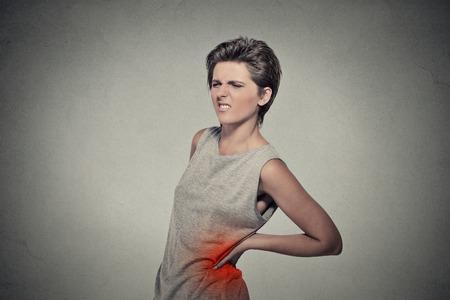 espalda: Mujer joven con dolor de espalda dolor de espalda hacia atr�s coloreado en rojo aislado sobre fondo gris