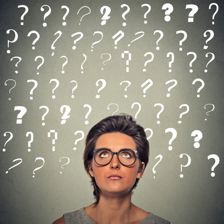 solution: Headshot woman with puzzled face expression and question marks above her head looking up isolated on gray wall background. Human emotions, feelings, body language, problem solution concept