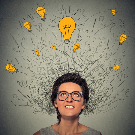 human head: Closeup thinking woman with question signs and light idea bulb above head looking up isolated on gray wall background