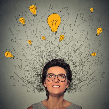 cabeza femenina: Pensamiento de la mujer del primer con signos de interrogación y la idea de la bombilla encima de la cabeza mirando hacia arriba aislados en el fondo gris de la pared