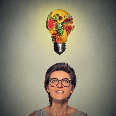 vision loss: Eating healthy idea and diet tips concept. Closeup portrait headshot woman looking up light bulb made of fruits above head on gray wall background.