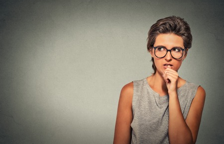 nervous: Closeup portrait nervous looking woman biting her fingernails craving something anxious isolated grey wall background with copy space. Negative human emotion facial expression body language perception Stock Photo