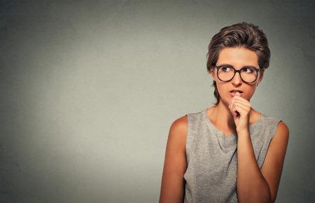 expresion corporal: Retrato del primer aspecto nervioso mujer que muerde sus uñas antojo de algo ansioso aislado fondo gris de la pared con copia espacio. Emoción humana Negativo expresión facial percepción lenguaje corporal