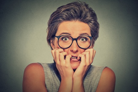 headshot nervous stressed young woman with glasses girl biting fingernails looking anxiously craving something isolated on gray wall background. Human emotion face expression feeling