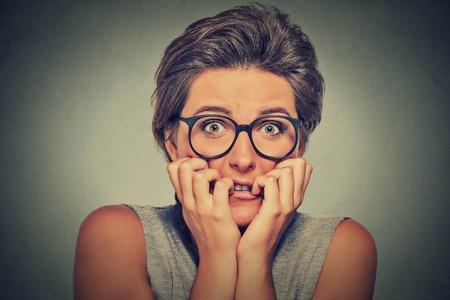 Kopfschuss nervös betonte junge Frau mit beißende Fingernägel Brille Mädchen ängstlich etwas auf grauen Wand Hintergrund Begierde suchen. Menschliche Emotionen Gesicht Ausdruck Gefühl