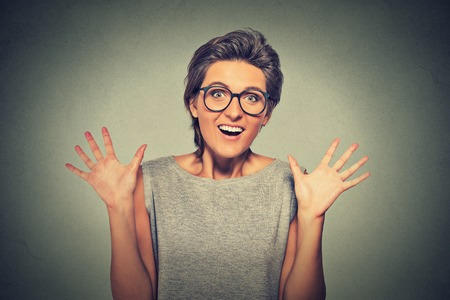 exaggerate: super excited funky young girl looking thrilled very happy isolated on grey wall background Stock Photo