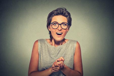 femme bouche ouverte: portrait Gros plan de jeune femme heureuse regardant excit� surpris en pleine incr�dulit� est moi? isol� sur gris fond mur. �motions humaines positives, la r�action des expressions du visage