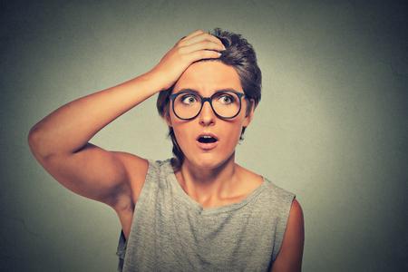 asombro: Sorpresa de la mujer sorprendida. Retrato del primer mujer con gafas mirando sorprendido en plena incredulidad amplia aislado boca abierta la pared de fondo gris. La emoción humana facial lenguaje corporal expresión. Foto de archivo
