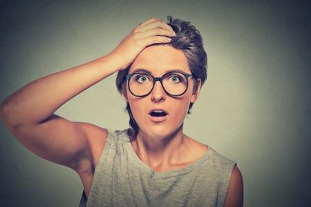 asombro: Sorpresa de la mujer sorprendida. Retrato del primer mujer con gafas mirando sorprendido en plena incredulidad amplia aislado boca abierta la pared de fondo gris. La emoci�n humana facial lenguaje corporal expresi�n. Foto de archivo