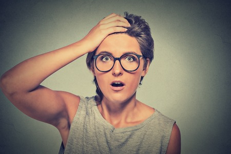 stunned: Surprise astonished woman. Closeup portrait woman with glasses looking surprised in full disbelief wide open mouth isolated grey wall background. Human emotion facial expression body language.