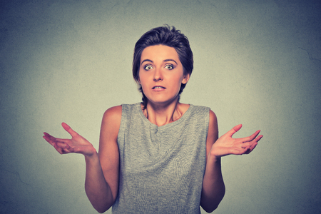 i dont know: Portrait dumb looking woman arms out shrugs shoulders who cares so what I dont know isolated on gray wall background. Negative human emotion, facial expression body language life perception attitude Stock Photo