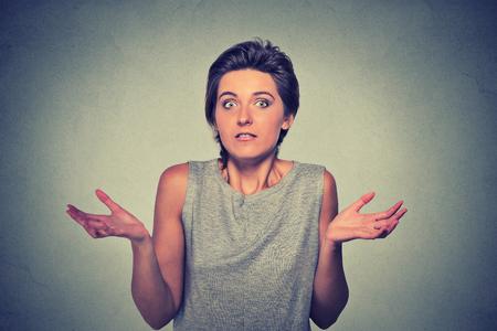 expresion corporal: Retrato tontos que buscan mujer brazos extendidos encoge los hombros que se preocupa por lo que lo que yo no lo sé aislado en el fondo gris de la pared. Las emociones humanas negativas, la expresión facial lenguaje corporal actitud percepción vida
