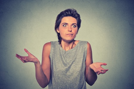 shrugs: Portrait dumb looking woman arms out shrugs shoulders who cares so what I dont know isolated on gray wall background. Negative human emotion, facial expression body language life perception attitude Stock Photo