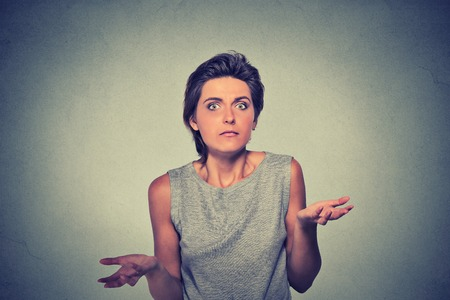 insensitive: Portrait dumb looking woman arms out shrugs shoulders who cares so what I dont know isolated on gray wall background. Negative human emotion, facial expression body language life perception attitude Stock Photo