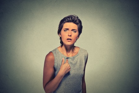 libel: Portrait angry, unhappy, annoyed young woman, getting mad asking question you talking to me, you mean me? Isolated on gray wall background. Negative emotions, facial expressions