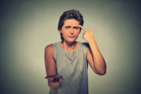 stupid body: Closeup portrait of angry mad young woman gesturing with her finger against temple asking are you crazy? Isolated on gray wall background. Negative emotions facial expression feeling body language