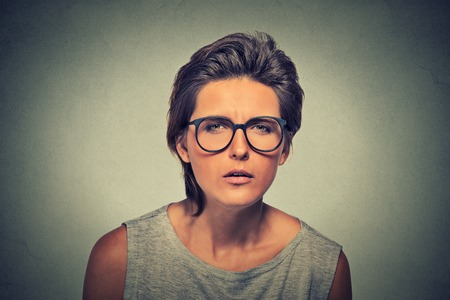 hostility: Displeased unsure arguable suspicious thinking young lady in glasses frowning wondering uncertain look gaze with hostility mistrust on gray wall background. Negative face expression emotion perception Stock Photo