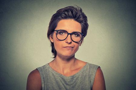 attitude: Escéptico. Malestar mujer enojada dudoso en los vidrios le mira la cámara aislada en el fondo gris de la pared. La expresión facial emoción humana Negativo sensación corporal actitud idioma Foto de archivo
