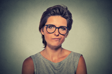 distrust: Skeptic. Doubtful upset angry woman in glasses looking at you camera isolated on gray wall background. Negative human emotion facial expression feeling body language attitude