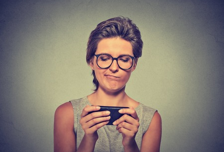 inappropriate: Portrait young angry woman with glasses unhappy, annoyed by something on cell phone while texting receiving bad sms text message isolated grey wall background. Human face expression emotion reaction