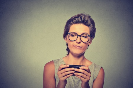 text: Portrait young angry woman with glasses unhappy, annoyed by something on cell phone while texting receiving bad sms text message isolated grey wall background. Human face expression emotion reaction