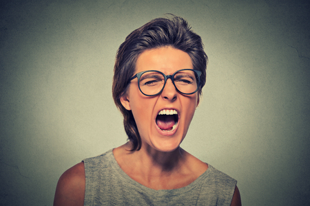 adult student: Angry young woman with glasses screaming Stock Photo