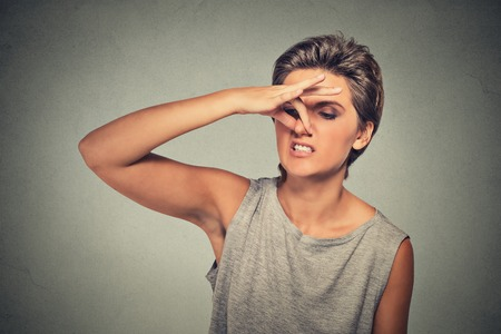pinches: headshot woman pinches nose with fingers hand looks with disgust away something stinks bad smell situation isolated on gray wall . Human face expression body language reaction