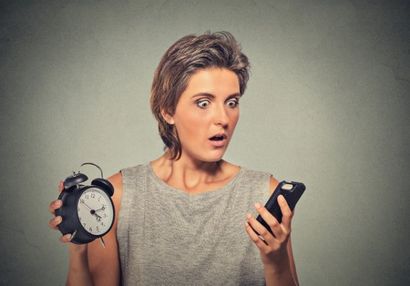 running late: Young woman with mobile phone and alarm clock stressed running late Stock Photo