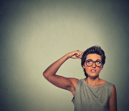 forgetful: Contused thinking woman with glasses bewildered scratching her head seeks a solution isolated on gray wall background. Young woman looking up Stock Photo