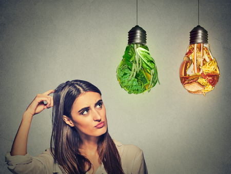 vegan food: Portrait beautiful woman thinking looking up at junk food and green vegetables shaped as light bulb isolated on gray background. Diet choice right nutrition healthy lifestyle concept