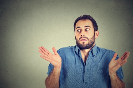 i don't know: Closeup portrait young man shrugging shoulders who cares so what I dont know gesture isolated on grey wall background. Body language Stock Photo