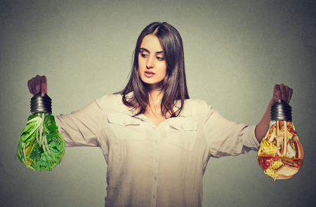 Woman thinking making diet choices junk food or green vegetables shaped as light bulb isolated on gray background. Right nutrition healthy lifestyle concept