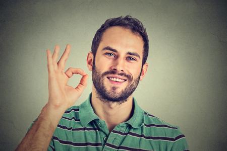 persona feliz: hombre gesticulando signo de OK aislado sobre fondo gris de la pared