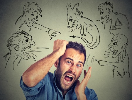 phobia: Evil men pointing at stressed anxious guy. Portrait desperate young businessman frustrated screaming isolated on grey wall background. Negative human emotions face expression feelings life perception