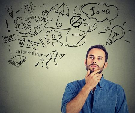 dream car: Retrato hombre de pensamiento joven sueños tiene muchas ideas mirando hacia arriba aislados fondo de la pared gris. Positivo expresión de la cara percepción sensación de emoción la vida humana. Toma de decisiones concepto de equilibrio trabajo vida.
