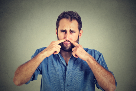 touch: portrait of disgusted man pinches nose with fingers hands looks with disgust something stinks bad smell situation isolated on gray wall background. Human face expression body language reaction Stock Photo