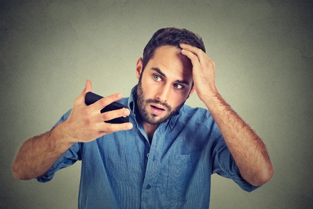 Closeup portrait, shocked man feeling head, surprised he is losing hair, receding hairline, bad news isolated on gray wall background. Negative facial expressions, emotion feeling Standard-Bild