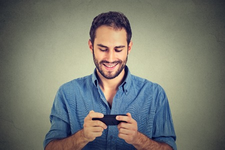 phone isolated: Smiling young man looking at his smart phone while text messaging or watching video, movie, pictures isolated on gray wall background. Positive face expression