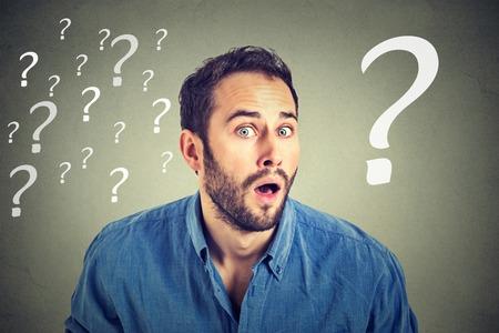 punto di domanda: Sorpreso uomo d'affari con molti punti interrogativi isolato su sfondo grigio muro
