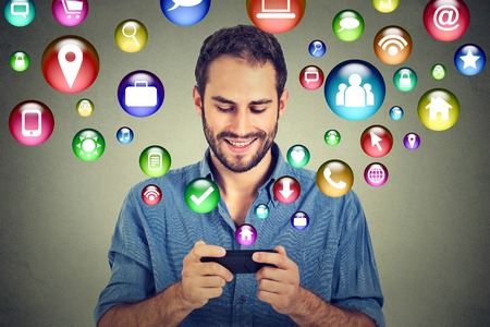 social: communication technology mobile phone high tech concept. Happy man using texting on smartphone social media application icons flying out of cellphone isolated grey wall background. 4g data plan Stock Photo